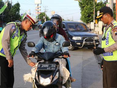 Petugas Kepolisian memberhentikan pengendara motor di Simpang Maya, Tegal, Jawa Tengah Minggu (10/7). Pemberhentian dilakukan untuk mengecek barang bawaan agar tidak membahayakan pengendara lain. (Liputan6.com/Herman Zakharia)