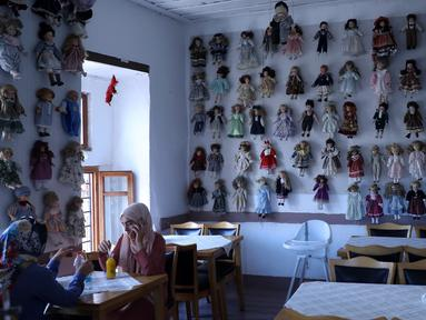 Pengunjung menikmati pesanan dengan boneka yang dipajang di kedai kopi Turki bernama Ankara Castle di Ankara, 8 Agustus 2019. Kedai kopi itu menyambut pengunjung dengan koleksi unik sebanyak 7.500 boneka porselen dari 81 negara yang dikumpulkan pemiliknya selama lebih dari 20 tahun. (Adem ALTAN/AFP)