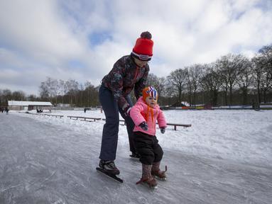 Seorang ibu mengajari putrinya berseluncur di gelanggang es di Doorn, Belanda, Selasa (9/2/2021). Dengan perkiraan suhu beku selama lebih dari seminggu di Belanda, demam es melanda Negeri Kincir Angin tersebut. (AP Photo/Peter Dejong)