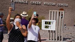 Orang-orang berswafoto dengan termometer di Pos Pusat Pengunjung Furnace Creek, Taman Nasional Death Valley, California, AS, Senin (17/8/2020). Temperatur udara tertinggi di Dunia -- 54,4 derajat Celcius -- tercatat di Taman Nasional Death Valley pada Minggu 16 Agustus. (AP Photo/John Locher)