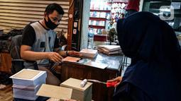 Aktivitas pedagang kertas undangan pernikahan di Pasar Tebet, Jakarta, Kamis (22/7/2020). Adanya larangan membuka toko dan juga berkerumun seperti pesta pernikahan menyebabkan pendapatan dari usaha percetakan ini turun drastis hingga 80 persen selama pandemi Covid-19. (Liputan6.com/Faizal Fanani)