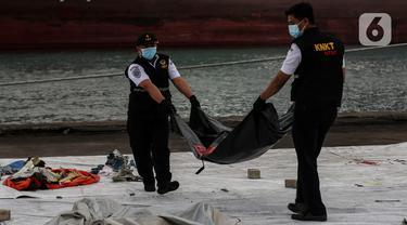 Petugas membawa kantong jenazah korban pesawat Sriwijaya Air SJ-182 yang jatuh di perairan Pulau Seribu, di Dermaga JICT, Jakarta, Selasa (12/1/2021). Pada hari keempat evakuasi ini petugas gabungan menyerahkan kantong-kantong berisikan, bagian tubuh, serpihan pesawat. (Liputan6.com/Johan Tallo)