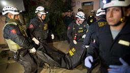 Petugas penyelamat membawa jenazah seorang turis setelah bus mengalami kecelakaan di Lima, Peru, (9/10). Pejabat Peru mengatakan sebuah bus wisata bersusun tidak terkendali dan berguling di jalan sempit di perbukitan. (AP Photo / Rodrigo Abd)