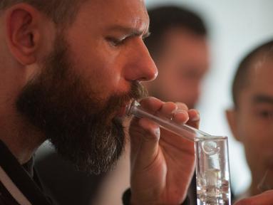 Seorang pria mengisap ganja saat peresmian Privee Social Club yang diadakan di rumah pribadi di Venesia, Los Angeles, California, AS, (23/3). Social Club adalah sebuah klub para pengguna ganja eksklusif. (AFP Photo / David Mcnew)