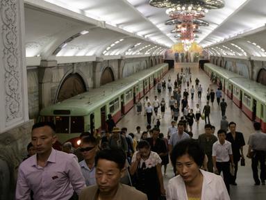 Para komuter berjalan melalui stasiun kereta bawah tanah atau metro Pyongyang di Korea Utara, 6 September 2018. Kereta bawah tanah Pyongyang Membentang sepanjang 22,5 km dengan 17 stasiun pemberhentian. (AFP / Ed JONES)