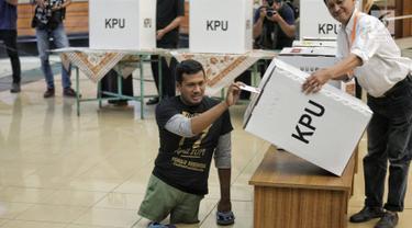 Penyandang disabilitas memasukkan surat suara ke dalam kotak saat simulasi Pemilu di Jakarta, Kamis (14/2). Simulasi ini digelar oleh Komisi Pemilihan Umum (KPU). (Liputan6.com/Faizal Fanani)