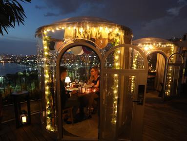 Pasangan menikmati makan malam mereka di zona aman yang disediakan sebuah restoran di Istanbul, Turki (16/6/2020). Sebuah restoran kelas atas di Sutluce, suatu kawasan di sisi Eropa Kota Istanbul, membuat pelanggannya merasa tenang di dalam zona aman. (Xinhua/Osman Orsal)