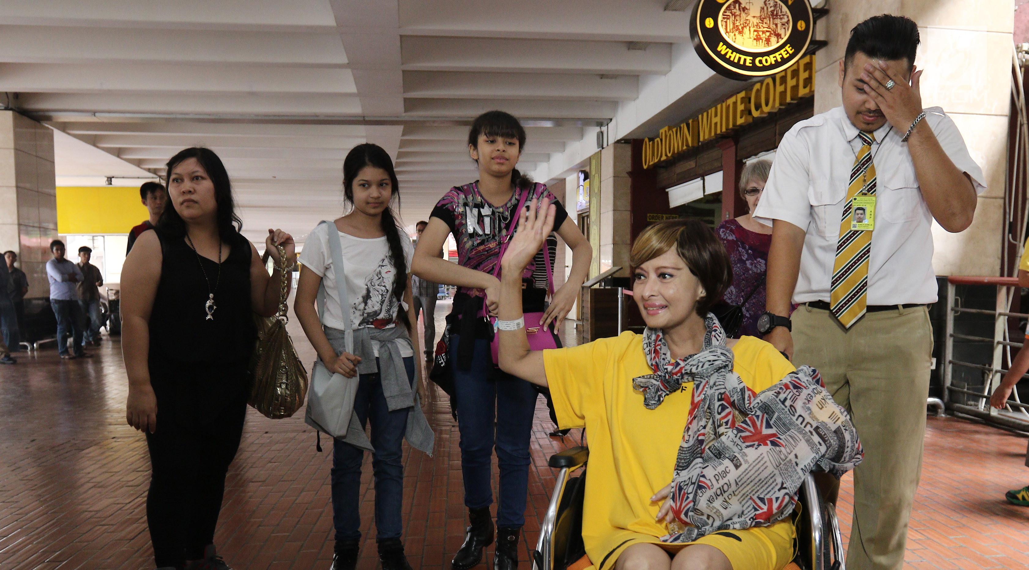 Pemain Sinetron Yana Zein melambaikan tangan saat tiba di bandara Bandara Soekarno Hatta, Tangerang, Minggu (28/5). Selama empat bulan Yana Zein mendapatkan perawatan intensif di Tiongkok, kondisinya jauh lebih baik.  (Liputan6.com/Herman Zakharia)