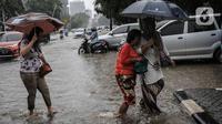 Pejalan kaki melintasi genangan air di Jalan Medan Merdeka Timur, Jakarta, Jumat (24/1/2020). Hujan deras yang mengguyur Jakarta sejak pagi tadi mengakibatkan genangan air di Jalan Medan Merdeka Timur. (Liputan6.com/Faizal Fanani)