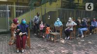 Sejumlah warga menunggu untuk divaksin di MTs As-Syafiiyah, Cilangkap, Jakarta, Kamis (3/6/2021).  Vaksinasi massal bagi warga RT 03/RW 03 Cilangkap, Cipayung, Jakarta Timur menggunakan vaksin produksi AstraZeneca. (Liputan6.com/Herman Zakharia)
