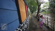 Warga melintas dekat tembok warna-warni di Kampung Penas Tanggul, Cipinang Besar Selatan, Jakarta, Kamis (23/3). Kampung warna-warni tanpa rokok itu dibuat warga sebagai bentuk upaya perlindungan bagi perempuan dan anak. (Liputan6.com/Immanuel Antonius)