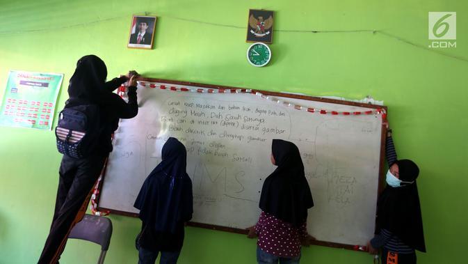 Sejumlah siswi memasang papan tulis yang jatuh akibat gempa di dalam kelas SMP Negeri 6 Palu, Sulawesi Tengah, Senin (8/10). Hari pertama sekolah pascagempa dan tsunami Palu, siswa belum memulai aktivitas belajar mengajar. (Liputan6.com/Fery Pradolo)