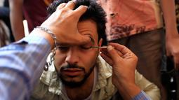 Seorang pria Yaman saat kelopak matanya dirias dengan kosmetik tradisional kohl di Masjid Agung, kota tua Sanaa pada 9 mei 2019. Bagi muslim Yaman, pemakaian kohl diyakini mampu membersihkan dan melindungi mata dari penyakit ini sudah menjadi tradisi setiap bulan Ramadan. (MOHAMMED HUWAIS/AFP)