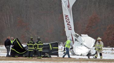 Tim penyelamat bekerja di lokasi kecelakaan pesawat kecil di Bandara Kota Mansfield, Massachusetts, AS, Sabtu (23/2). Kecelakaan menewaskan dua orang. (Matthew J. Lee/The Boston Globe via AP)