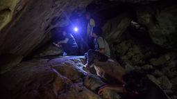 Arkeolog dari Departemen Seni Rupa melihat lukisan gua yang baru ditemukan di taman nasional Khao Sam Roi Yot di pesisir provinsi Prachuap Kiri Khan (10/9/2020). Kanniga menyorotkan senternya ke seluruh gua untuk mengungkap lukisan yang diyakini berasal dari era prasejarah. (AFP/Lillian Suwanrumpha)