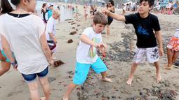 Sejumlah pengunjung terlihat bermain dengan beberapa dari ribuan kepiting tuna merah yang terdampar di sepanjang pantai Dana Point, California, Rabu (17/6/2015). (REUTERS/Sandy Huffaker)