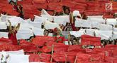 Suporter Indonesia berdiri diantara koreografi bendera Merah Putih jelang menyaksikan laga Indonesia lawan Laos pada penyisihan Grup A Sepak Bola Asian Games 2018 di Stadion Patriot Candrabhaga, Bekasi, Jumat (17/8). (Liputan6.com/Helmi Fithriansyah)