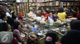 Sejumlah calon pembeli mengantre membeli kue kering di Pasar Jatinegara, Jakarta, Senin (27/6). Alasan warga membeli panganan khas lebaran di toko kue karena lebih praktis dan terjangkau harganya. (Liputan6.com/Faizal Fanani)