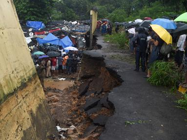 Petugas penyelamat dan warga berkumpul di lokasi runtuhnya tembok di Mumbai, India (2/7/2019). Sedikitnya 15 orang tewas dan 69 orang lainya luka ketika sebuah tembok runtuh saat hujan lebat monsun. (AFP Photo/Punit Paranjpe)