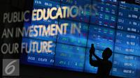 Pengunjung melintas di dekat monitor perkembangan saham di Bursa Efek Indonesia, Jakarta, Senin (2/11).  Indeks Harga Saham Gabungan (IHSG) di Bursa Efek Indonesia (BEI) pada Senin dibuka melemah sebesar 12,76 poin. (Liputan6.com/Immanuel Antonius)
