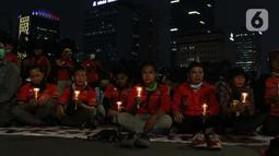 Beberapa peserta aksi unjuk rasa memegang lilin saat doa bersama lintas agama di Kawasan Patung Kuda, Jakarta, Selasa (10/11/2020). Sejumlah massa gabungan dari berbagai organisasi buruh dan mahasiswa berunjuk rasa menolak pengesahan Omnibus Law UU Cipta Kerja. (Liputan6.com/Helmi Fithriansyah)