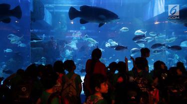 Anak - anak sekolah melihat ikan di dalam aquarium saat peresmian Jakarta Aquarium di Neo Soho, Jakarta, Selasa (16/10). Taman Safari Indonesia bekerjasama dengan Aquaria resmi membuka Jakarta Aquarium. (Liputan6.com/Johan Tallo)