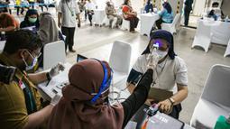 Petugas kesehatan memeriksa suhu tubuh seorang pemuka agama sebelum menjalani Vaksinasi COVID-19 di Mesjid Istiqlal, Jakarta, Selasa (23/2/2021). Para pemuka agama itu berasal dari seluruh wilayah di Jakarta. vaksinasi akan berlangsung selama dua hari. (Liputan6.com/Faizal Fanani)