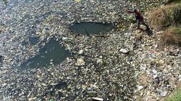 Warga mencari sampah plastik untuk didaur ulang di aliran Sungai Citarum, Bandung, Jawa Barat, Rabu (26/6/2019). Berbagai upaya dilakukan pemerintah untuk membersihkan sungai yang menyandang predikat salah satu tempat paling tercemar di dunia ini. (Timur Matahari/AFP)