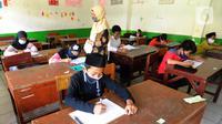 Guru mengawasi murid kelas V saat menjalani ujian Penilaian Akhir Semester (PAS) tahun pelajaran 2020/2021 di Madrasah Ibtidayah (MI) Assu'ada di Pancoran Mas, Depok, Jawa Barat, Selasa (1/12/2020). Ujian dilaksanakan dengan menerapkan protokol kesehatan dalam kelas. (merdeka.com/Arie Basuki)