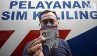 Warga menunjukkan SIM di Pelayanan SIM Keliling, Tangerang Selatan, Banten, Jumat (7/8/2020). Ditlantas Polda Metro Jaya memberi dispensasi bagi pemilik SIM yang masa berlakunya habis di masa pandemi COVID-19 bisa memperpanjang sampai akhir Agustus 2020. (merdeka.com/Dwi Narwoko)