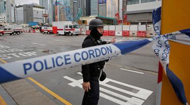 Tim penjinak bom dari kepolisian Hong Kong dikerahkan mengamankan bom sisa Perang Dunia II di sebuah lokasi konstruksi di distrik Wan Chai, Rabu (31/1). Penemuan bom seberat 450 kg tersebut memaksa dilakukannya evakuasi ribuan warga. (AP/Kin Cheung)