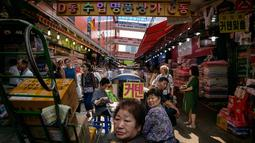 Sejumlah pengunjung berjalan di antara kios di pasar Namdaemun di Seoul (2/7/2019). Di dalam pasar ini, terdapat 58 buah bangunan yang melingkupi sekitar 9000 buah toko yang menjual berbagai jenis barang dalam harga yang murah. (AFP Photo/Minji Suh)