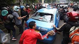 Sejumlah ojek online mengunakan batu merusak taksi di kawasan Senayan, Jakarta, Selasa (22/3). Pascabentrok ojek online melakukan sweeping dan perusakan terhadap taksi serta bajaj yang melintas di kawasan tersebut. (Liputan6.com/Immanuel Antonius)