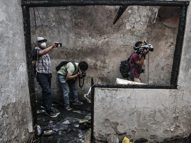 Awak media mengambil gambar di lokasi kebakaran yang melanda rumah kontrakan di Jalan Pisangan Baru III, RT 006/010, Matraman, Jakarta, Kamis (25/3/2021). Kebakaran yang diduga terjadi karena korsleting listrik tersebut menghanguskan 5 rumah kontrakan. (merdeka.com/Iqbal S. Nugroho)