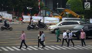 Warga menyeberang jalan dekat proyek pelebaran jalur khusus pejalan kaki atau pedestrian di kawasan Sarinah, Jakarta, Rabu (4/7). Pelebaran ini dilakukan untuk menyambut Asian Games 2018. (Merdeka.com/Imam Buhori)