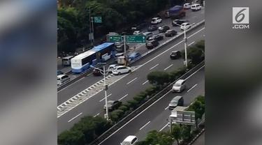 Beberapa mobil melakukan pelanggaran lalu lintas dengan berjalan mundur memasuki tol.