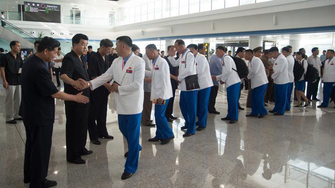 Atlet Korut yang dikepalai Wakil Menteri Olahraga Korea Utara, Won Kil U bersiap meninggalkan bandara internasional Pyongyang, Korut (10/8). Korut akan berpartisipasi dalam Asian Games 2018 di Jakarta dan Palembang, Indonesia. (AFP Photo/Kim Won-Jin)