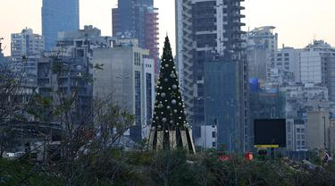 Sebuah pohon Natal dengan daftar nama korban yang tewas dalam insiden ledakan di Pelabuhan Beirut terlihat di dekat silo gandum yang rusak di Beirut, Lebanon (22/12/2020). Dua ledakan besar mengguncang Pelabuhan Beirut pada 4 Agustus lalu. (Xinhua/Bilal Jawich)