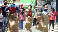 Anak-anak mengikuti lomba balap karung saat acara kegiatan tujuh belas Agustus di Cinere, Depok, Senin (17/8/2020). Warga di sejumlah kampung di wilayah Jabodetabek tetap melakukan beragam kegiatan lomba memperingati HUT ke-75 RI dengan menerapkan protokol kesehatan. (merdeka.com/Arie Basuki)