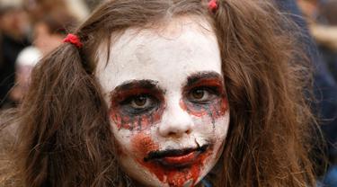 Seorang anak berpose dengan dandanan menyerupai zombie ketika berpartisipasi dalam 'Zombie Walk' di pusat Kota Kiev, Ukraina, 26 Oktober 2019. Menjelang perayaan Halloween pada 31 Oktober mendatang, warga di beberapa belahan dunia sudah mulai melakukan acara bertema horor. (AP/Efrem Lukatsky)