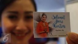 Pramugari menunjukkan kartu ucapan di Pesawat Garuda Indonesia menuju, Padang, Sumatera Barat, Jumat (21/4). Menyambut Hari Kartini, penerbangan Garuda Indonesia diawaki seluruhnya oleh perempuan. (Liputan6.com/Angga Yuniar)