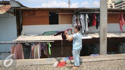 Seorang warga menjemur pakaian di kawasan Kampung bandan, Jakarta, Selasa (28/7/2015). Pemprov DKI Jakarta berencana menata sekitar Stasiun dengan membangun rumah susun yang memanfaatkan lahan milik PT KAI. (Liputan6.com/Faizal Fanani)