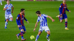 Striker Barcelona, Lionel Messi, berusaha melewati pemain Real Sociedad, Ander Guevara, pada laga Liga Spanyol di Stadion Camp Nou, Kamis (17/12/2020). Barcelona menang dengan skor 2-1. (AP/Joan Monfort)