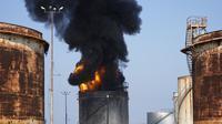 Petugas pemadam kebakaran memadamkan api di fasilitas minyak di selatan kota Zahrani, selatan kota pelabuhan Sidon, Lebanon, Senin, 11 Oktober 2021. (AP Photo)