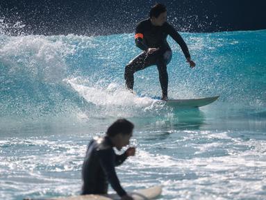 Peselancar meniti ombak di kolam ombak Wave Park di Siheung, Korea Selatan pada 18 Oktober 2020. Korea Selatan memiliki kolam ombak terbesar di dunia dengan teknologi Wavegarden Cove yang memiliki beberapa modul produksi gelombang dan menjadi kolam gelombang dengan jumlah terbesar. (Ed JONES/AFP)