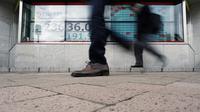 Orang-orang berjalan melewati layar monitor yang menunjukkan indeks bursa saham Nikkei 225 Jepang dan lainnya di sebuah perusahaan sekuritas di Tokyo, Senin (10/2/2020). Pasar saham Asia turun pada Senin setelah China melaporkan kenaikan dalam kasus wabah virus corona. (AP Photo/Eugene Hoshiko)