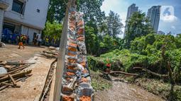 Aktivitas petugas UPK Badan Air DLH Provinsi DKI Jakarta saat memperbaiki tembok Kali Krukut yang jebol di Jalan Taman Kemang, Jakarta, Selasa (23/2/2021). Jebolnya tembok tersebut mengakibatkan kawasan kemang dan sekitarnya terendam banjir pada 20 Februari 2021. (Liputan6.com/Faizal Fanani)
