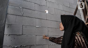 Wiwiek (56) menunjukkan tembok sekolah Pendidikan Perguruan Nasional (Pergunas) I yang menutup akses rumahnya di Jalan Cempaka Baru I, RT 015/003, Kemayoran, Jakarta, Senin (31/8/2020). Pembangunan itu menutup akses jalur keluar masuk dan harus melewati pintu samping. (merdeka.com/Iqbal S Nugroho)