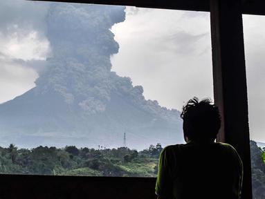 Penduduk desa melihat asap abu vulkanik Gunung Sinabung dari kota Karo (6/4). Gunung Sinabung di Kabupaten Karo, Sumatera Utara, kembali meletus, pada Jumat (6/4/2018) pukul 16.07 WIB. (AFP Photo/Anto Sembiring)