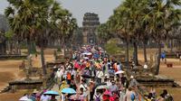 Turis mengunjungi candi Angkor Wat di provinsi Siem Reap, barat laut Kamboja pada 16 Maret 2019. Angkor Wat merupakan salah satu obyek wisata favorit dunia yang dibangun pada abad ke-12 Masehi. (TANG CHHIN Sothy / AFP)